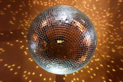 Mirror disco ball. Reflecting yellow spotlight against black background stock photo