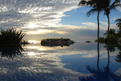 Mirror effect in endless pool Los Cabos. Sunrise with light cloud cover mirrored in pool stock image
