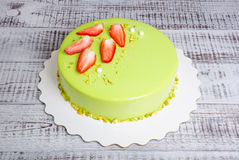 Mirror glaze mousse cake with strawberries and pistachios. A mirror glaze mousse cake with strawberries and pistachios Royalty Free Stock Photo