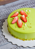 Mirror glaze mousse cake with strawberries and pistachios Royalty Free Stock Image