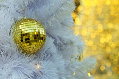 Mirror Golden Christmas ball items on white pie and yellow bokeh form LED lighting background. Royalty Free Stock Photos