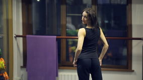 Before the mirror in the gym slim woman looking at herself. Caucasian woman dissolve dark long hair, which have wave. It examines the front and rear of the stock footage