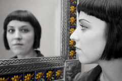 Mirror Image. Reflection of a young woman in a mirror, using selective colour Stock Images
