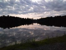 Mirror image of the trees and sky on the water. Mirror image of the trees and sky on the lake stock images