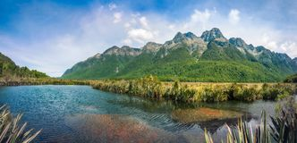 Mirror Lake Panorama in New Zealand. Mirror Lake with mountain range in the background in Fiordland National Park, New Zealand, South Island Stock Photo