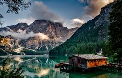Mirror Lake Reflecting Wooden House in Middle of Lake Overlooking Mountain Ranges Royalty Free Stock Photography