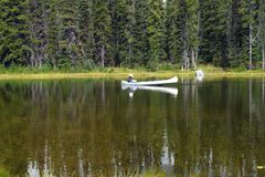 Mirror Lake and a white canoe fisherman. Royalty Free Stock Photos