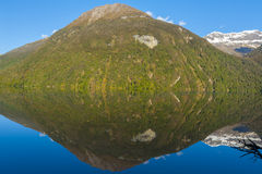 Mirror Lakes. Are a famous natural landmark omn the Milford Road in the Fiordland National Park. Snowy mountains are reflecting in a calm water. New Zealand royalty free stock images