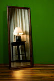 Mirror with lamp in green room. Green room with lamp in mirror Stock Photo