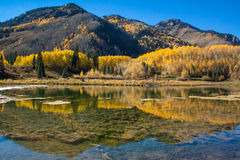 Mirror like reflection in a clear lake, reflecting mountains with Autumn colors Stock Images