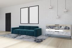 Mirror living room corner, blue sofa, side. White wall living room corner with a soft carpet, a blue sofa with two posters hanging above it and a marble chest of Royalty Free Stock Photos