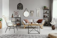 Mirror, macrame and graphic on the grey wall of warm ethno living room. With stylish furniture and cozy patterned carpet royalty free stock images