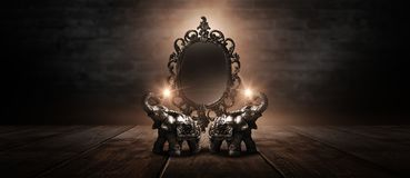 Mirror magical, fortune telling and fulfillment of desires. Golden elephant on a wooden table. Dark room, light effect. Beautiful statuette of an elephant on stock photography