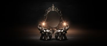 Mirror magical, fortune telling and fulfillment of desires. Golden elephant on a wooden table. Dark room, light effect. Beautiful statuette of an elephant on stock images