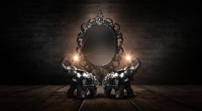 Mirror magical, fortune telling and fulfillment of desires. Golden elephant on a wooden table. Dark room, light effect. Beautiful statuette of an elephant on stock photos