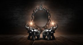 Mirror magical, fortune telling and fulfillment of desires. Golden elephant on a wooden table. Dark room, light effect. Beautiful statuette of an elephant on royalty free stock image