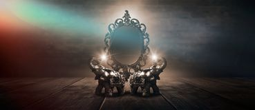 Mirror magical, fortune telling and fulfillment of desires. Golden elephant on a wooden table. stock photo