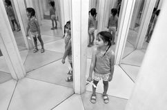 Mirror maze. Little child (girl age 05) inside Mirror maze.(BW Stock Photo