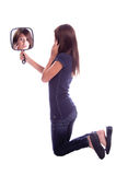 Mirror-Mirror. Portrait of a Pretty young girl (11 years old) sitting on the floor and looking at herself in a hand mirror Stock Photos