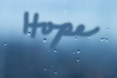 Mirror with mist and rain drop with the word 'Hope' hand writing. Mirror with mist and rain drop background in dark blue color with word 'Hope' in hand Stock Images
