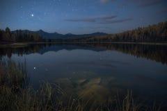 Mirror Oberflächensee Autumn Landscape With Mountain Range in frühem Eveing mit Sternen auf dem Himmel Stockbilder
