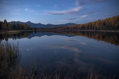 Mirror Oberflächensee Autumn Landscape With Mountain Range in frühem Eveing mit Sternen auf dem Himmel Stockbild