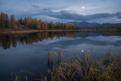 Mirror Oberflächensee Autumn Landscape With Mountain Range in frühem Eveing mit Sternen auf dem Himmel Stockfotos