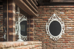 The mirror on the old brick wall Stock Photo