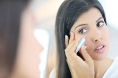 Mirror portrait of young woman applying concealer Stock Photography