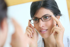 Mirror portrait of young woman trying on eyeglasses Royalty Free Stock Photos