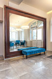 Mirror and a pouf. Huge mirror with wooden frame and turquoise pouf royalty free stock images