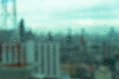 Mirror with rain drops with blur of urban background Stock Image