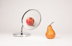 Mirror reflecting apple and pear. Strange mirror reflecting apple and pear Royalty Free Stock Image