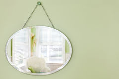 Mirror reflecting room. Oval mirror hanging on the wall in a summery beach house sitting area royalty free stock photos