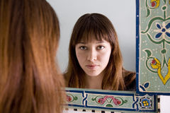 Mirror Reflection. Attractive young woman seen as a reflection in an ethnic style mirror Royalty Free Stock Photography