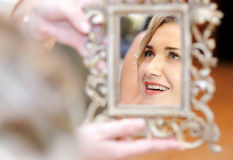 Mirror reflection. Smiling woman portrait reflecting in a mirror Stock Images