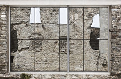 Mirror reflection on an ancient stone wall facade in Spain Royalty Free Stock Images