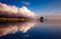 A mirror reflection of a beach. A clear mirror reflection of clouds and sea stack rock on a smooth beach Royalty Free Stock Image