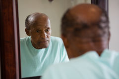 Mirror with reflection of concerned senior man Stock Photography