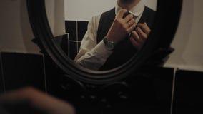 Elegant businessman prepares suit in mirror stock video