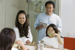 Mirror reflection of Family in Bathroom Getting Ready for Day daughter brushing teeth Royalty Free Stock Images