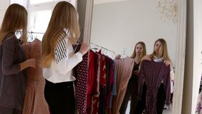 Mirror reflection footage of a young, beautiful girl in clothes shop trying the fashion dress trying on on top on her. Clothes, exciting about her look. Slow stock footage