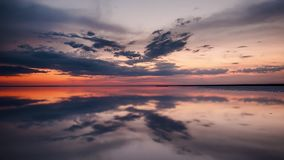 Mirror reflection on the lake. Sunset reflects in the watery surface of Lake Elton.