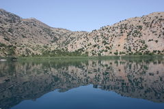 Mirror reflection of the mountains in the lake water. Mirror reflection of the mountains in the mountain lake water with narrowing In the middle and blue water Royalty Free Stock Photo