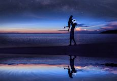 Free Mirror Reflection Of Silhouette Father And Daughter On The Beach With Million Stars Galaxy And Blue Sky Early Morning Stock Images - 145733524
