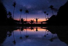 Mirror reflection of Panoramic landscape of man standing on the coconut beach with a million stars and sunrise early. Morning royalty free stock photos