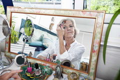 Mirror reflection of senior woman applying blusher at home Stock Images