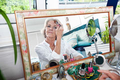 Mirror reflection of senior woman applying blusher at home Stock Photos