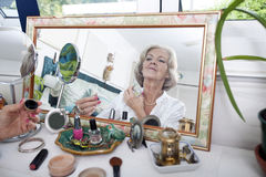 Mirror reflection of senior woman spraying perfume on herself at home Royalty Free Stock Photo