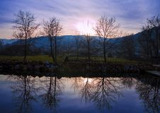 In the mirror. A reflection of trees and sunset in the River Gradac, Valjevo, Serbia Stock Image